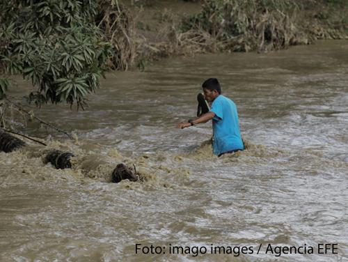Ein Mann versucht eine überschwemmte Brücke in Honduras zu überqueren. Der Wirbelsturm Iota hat die Brücken dort überschwemmt.