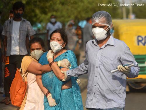 Zwei Frauen weinen um einen Angehörigen, der in Indien an Corona verstorben ist.
