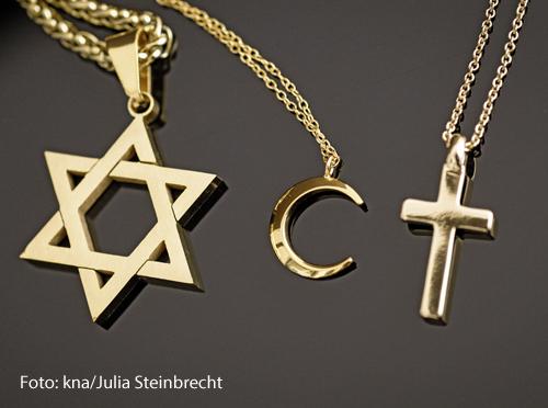 Ein goldener Davidstern, ein Halbmond und ein Kreuz liegen nebeneinander.