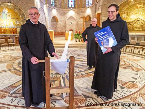 Drei Mönche zeigen eine lange Papierrolle, auf der Gebetsanliegen stehen.