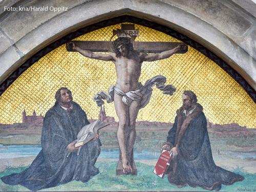Kreuzigungsdarstellung an der Thesentür der Schlosskirche in der Lutherstadt Wittenberg am 31. März 2017. Neben Christus am Kreuz knien Martin Luther und Melanchton.