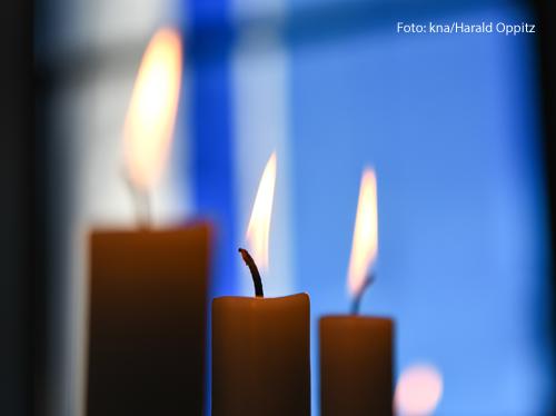 Brennende Kerzen stehen vor einem Fenster.