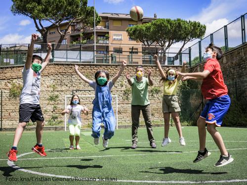 Kinder spielen auf einem Fußballplatz.