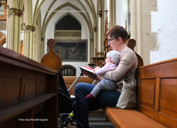 Eine Mutter sitzt mit ihrem Kind in einer Kirchenbank.