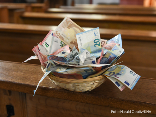 Ein Korb mit Geld steht in einer Kirchenbank.
