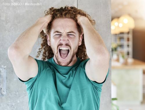 Ein Mann hält sich die Hände an den Kopf und schreit.