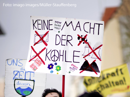 """Ein Demonstrant hält bei einer Klimademonstration ein Plakat hoch. """"Keine Macht der Kohle"""" steht darauf."""