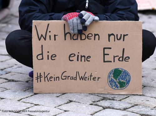Ein Demonstrant mit dem Plakat: Wir haben nur eine Erde!