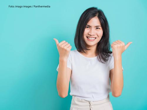 Eine Frau hält zwei Daumen in die Höhe und lächelt fröhlich.