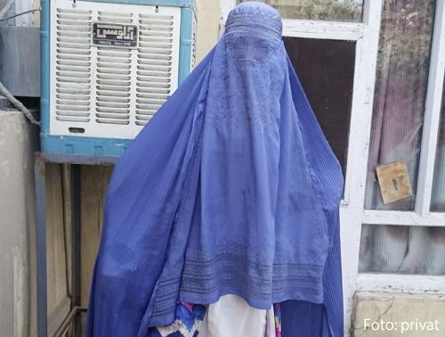 Eine junge Frau ist unter einem blauen Schleier verhüllt.
