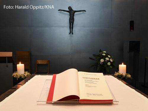Ein Lektionar liegt aufgeschlagen auf einem Tisch. Im Hintergrund hängt ein Kruzifix.