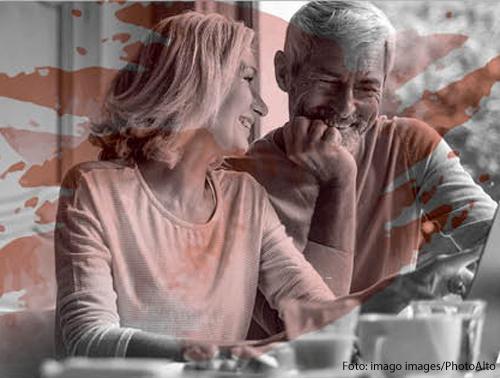 Ein älteres Paar sitzt verliebt vor einem Computer.