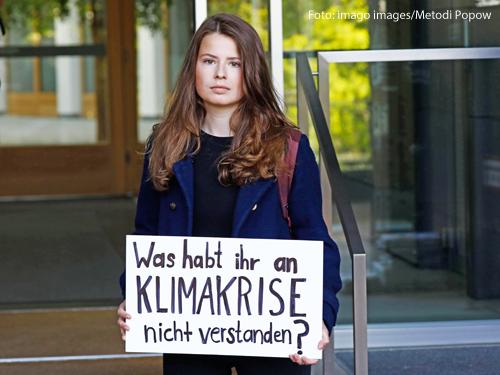 """Die Klimaaktivistin Luisa Neubauer hält vor dem Bundeskanzleramt ein Schild in die Höhe. Darauf steht: """"Was habt ihr an Klimakrise nicht verstanden?"""""""