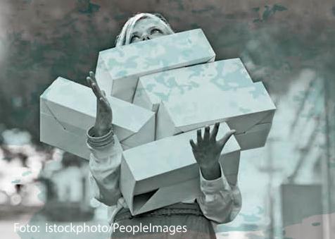 Eine Frau trägt aufeinandergestapelte Kartons.