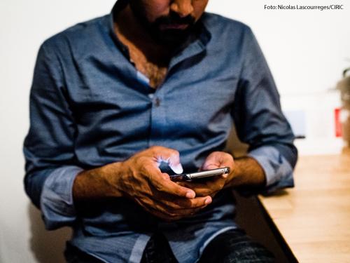 Ein Mann schaut auf sein Smartphone.