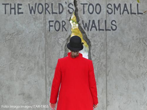 Eine Frau geht durch den Riss einer Mauer. Sie trägt einen schwarzen Hut und einen roten Mantel.