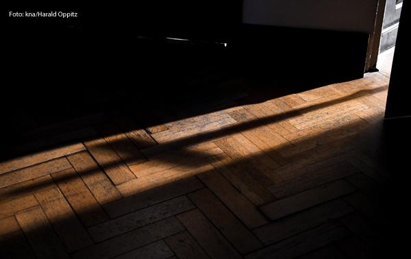 Der Schatten eines Kreuzes fällt auf einen dunklen Boden.
