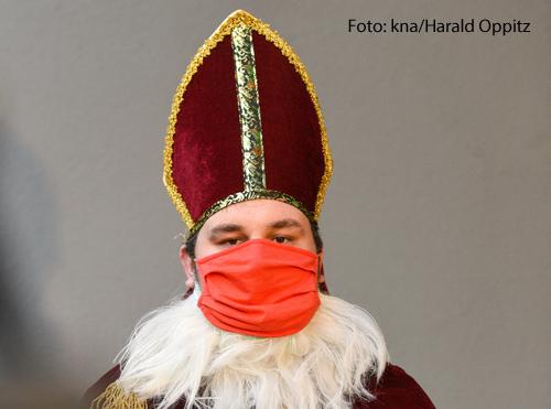 Ein Mann trägt ein Nikolaus-Kostüm und einen Mundschutz.