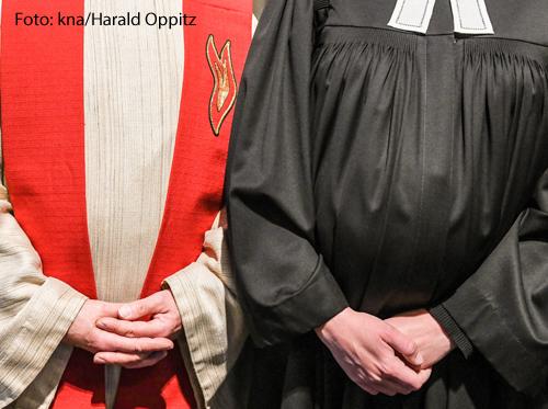 Ein katholischer Priester und ein evangelischer Pastor stehen nebeneinander.