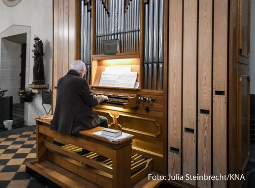 Ein Organist spielt eine Orgel.