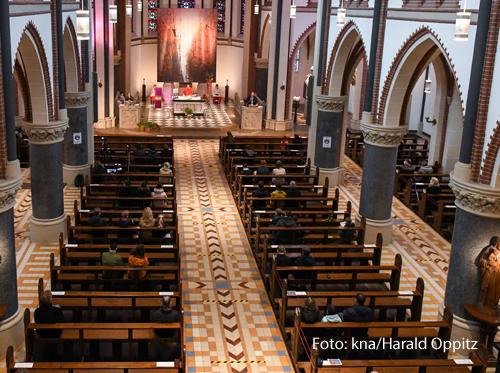 Blick von oben auf halbleere Kirchenbänke mit wenigen Gottesdienstteilnehmern während eines Gottesdienstes