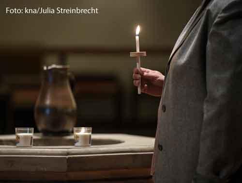 Eine Frau steht einer brennenden Kerze in einer dunklen Kirche. Sie nimmt an einer Osternacht teil.