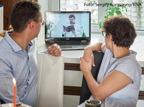 Ein Mann und eine Frau sitzen am Frühstückstisch und sehen sich auf dem Laptop einen Gottesdienst an