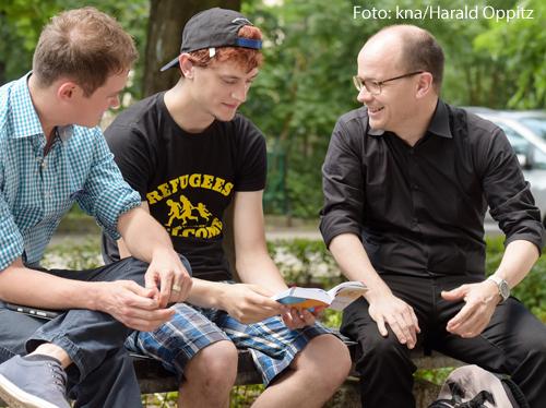 Ein Parrer unterhält sich mit zwei Jugendlichen.