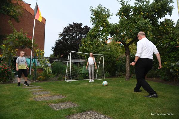 Ein Pfarrer spielt mit Kindern Fußball.