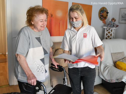 Eine Mitarbeitern der Ambulanten Pflege der Caritas trägt Mundschutz und spricht mit einer Patientin in deren Wohnung in Bonn.
