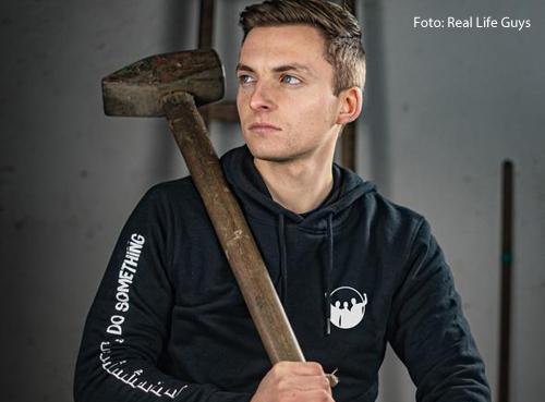 Phillip Mickenberger hält einen großen Hammer in der Hand. Erveröffentlicht Videos auf Youtube, in denen er verrückte Objekte baut.