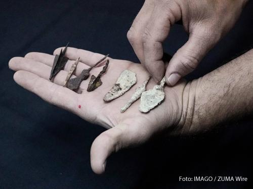 Eine Archäologin hält Fragmente einer biblischen Schriftrolle in der Hand. Forscher haben sie in der judäischen Wüste gefunden.