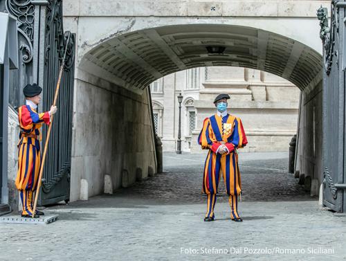 Zwei Mitglieder der Schweizergarde stehen mit Mundschutz vor einem Gebäude des Vatikan.