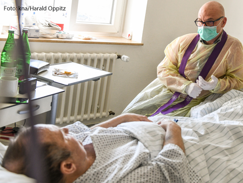 Ein Seelsorger sitzt am Bett eines Covid19-Patienten.