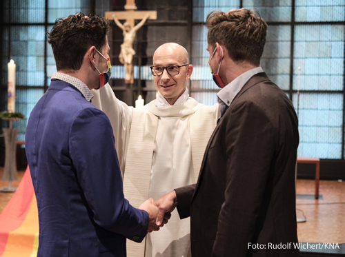 """Priester Christian Olding segnet ein homosexuelles Paar beim Segnungsgottesdienst """"Liebe gewinnt"""" in der Kirche Sankt Martin in Geldern am 6. Mai 2021. Am Altar hängt eine Regenbogenfahne."""