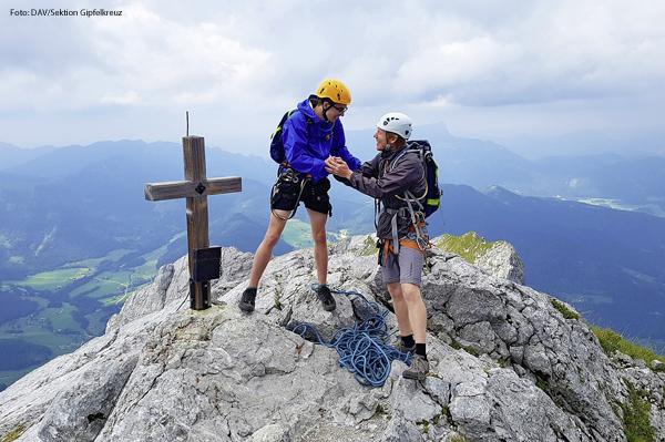 """Zwei Bergsteiger der Sektion """"Gipelkreuz"""" des Deutschen Alpenvereins stehen auf einem Gipfel."""