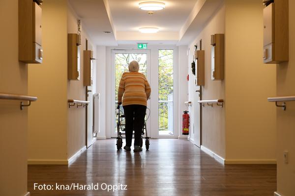 Eine Seniorin läuft in einem Altenheim über einen Flur.