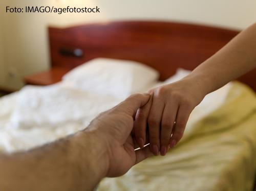 Ein Mann und eine Frau halten einander bei den Händen. Im Hintergrund ist ein Bett zu sehen.