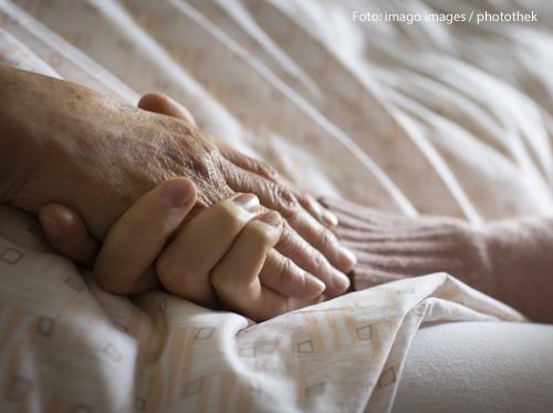 Eine Frau hält die Hand einer Patientin in einem Pflegeheim.