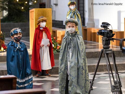 Kinder, die als Sternsinger gekleidet sind drehen in einer Bonner Kirche ein Video. Neben ihnen steht eine Kamera auf einem Stativ.