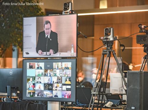 Bischof Georg Bätzing, Vorsitzender der Deutschen Bischofskonferenz (DBK), ist auf einem Monitor abgebildet im Regiezentrum der Online-Konferenz des Synodalen Weges am 4. Februar 2021 im Foyer der DBK in Bonn. Darunter ein Bildschirm mit Teilnehmern der Konferenz.
