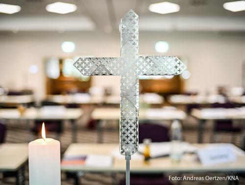 """Eine brennende Kerze und ein gelochtes Metallkreuz vor dem noch leeren Tagungsraum der Regionenkonferenz """"Fünf Orte - ein Weg"""" zum synodalen Weg am 4. September 2020 in Dortmund."""