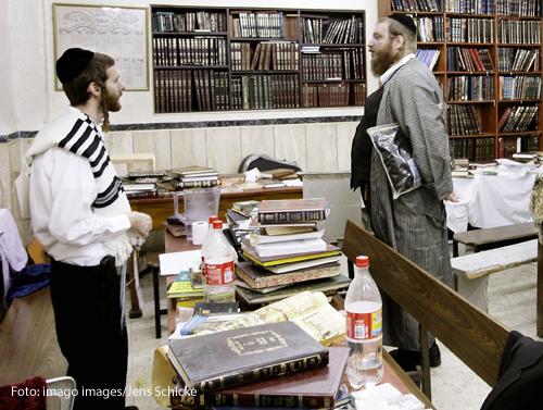 Zwei Männer stehen in Mitten von Büchern in einer Talmudschule in Mea Shearim, dem ultraorthodoxen Stadtviertel von Jerusalem.