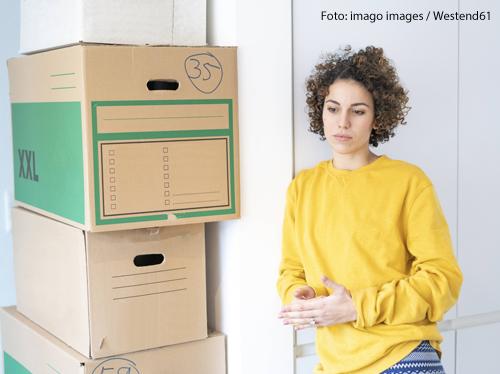 Eine Frau steht neben gepackten Umzugskartons. Sie sieht nachdenklich aus.