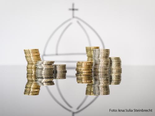 Geldmünzen vor einer Kuppel des Petersdoms symbolisieren die Finanzen des Vatikans.