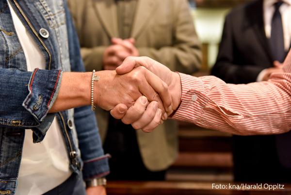 Zwei Frauen reichen sich die Hand.