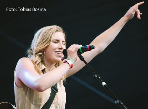 Eine junge Frau steht auf einer Bühne und singt in ein Mikrofon.