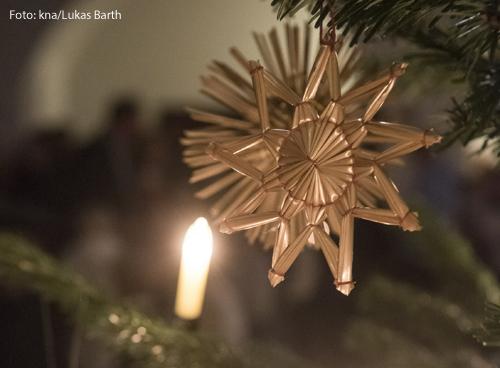 Eine Kerze und ein Stern an einem Christbaum