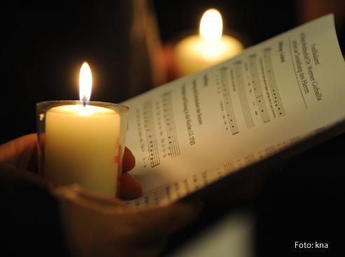 Eine Frau hält einen Liedzettel und eine Kerze in der Hand.