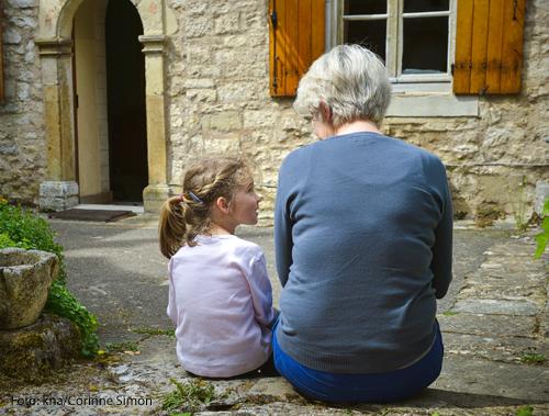 Eine Großmutter ist im Gespräch mit ihrer Enkelin. Sie sitzt auf einer Mauer.